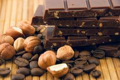 chocolate and nuts on a bamboo mat - stock photo