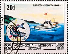 Postage stamp shows boat and fish Stock Photos