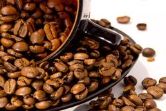 Cup and saucer with the coffee beans isolated on white Stock Photos