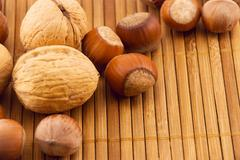 nuts on a bamboo mat - stock photo