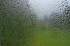Water condensation and rain drops pattern on a window. - stock photo