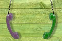 handsets hung against wooden wall - stock photo