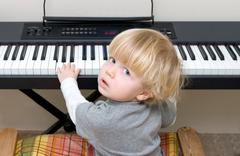 Young boy playing piano or keyboard Stock Photos
