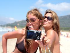 Two pretty young girlfriends taking a photo of themselves with camera - stock photo