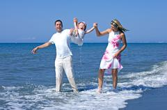 Young family playing with daughter on beach in spain Stock Photos