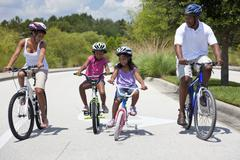 African american family parents and children cycling Stock Photos