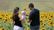 Young family near sunflower field Stock Footage