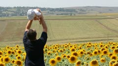 Father raising his baby near a sunflower field Stock Footage