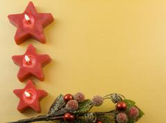 three red star candles with berry accent - stock photo