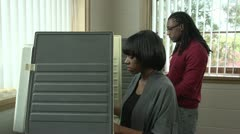 Voting, young female and male African American in voting booths Stock Footage