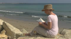 Beautiful woman reading drinking white wine on the beach ocean sea book young  Stock Footage