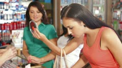 Sales Person Assisting Female Shoppers in Choice of Cosmetics Stock Footage