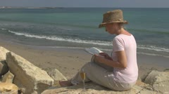 Woman reading drinking white wine on the beach lifestyle book sitting rock ocean Stock Footage