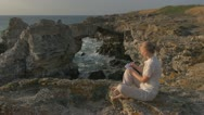 Beautiful woman drawing on the beach relax lifestyle paradise resort rock stone Stock Footage