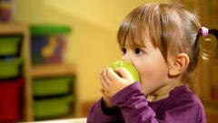Babies and food, female child eating green apple in kindergarten Stock Footage