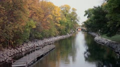 Fall Trees and River with Dock and Stone Bridge Stock Footage