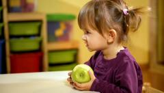 Baby and food, little girl eating green apple at school Stock Footage