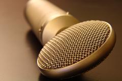 Silver Lollipop Microphone on Dark Tabletop - stock photo