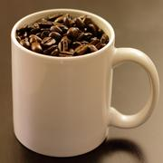 Coffee Mug Full of Whole Coffee Beans - stock photo