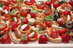 lot of canape with  shrimp, caviar, strawberries and other on wooden tray, se - stock photo