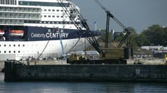 Heavy crane slowly moving boom extended, ships dock Stock Footage