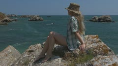 Young woman relaxing on the beach, coastline rock sitting stone summer trip Stock Footage