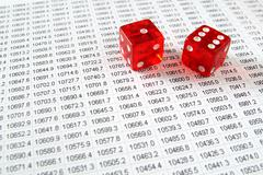 Two red dice on a spreadsheet financial data print out. Stock Photos