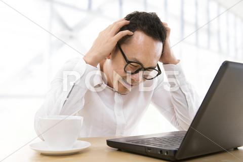 Stock photo of depressed asian business man