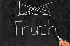 crossing out lies and writing truth on a blackboard. - stock photo