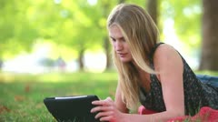 Young woman with tablet computer on grass - stock footage