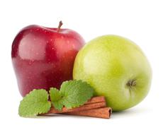 red and green apples, cinnamon sticks and mint leaves still life - stock photo
