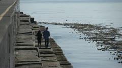 A couple walking along Ogden Point breakwater Stock Footage