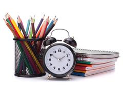 Alarm clock, notebook stack and pencils. schoolchild and student studies acce Stock Photos
