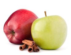 Red and green apples, cinnamon sticks and mint leaves still life Stock Photos