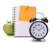 alarm clock, blank notebook sheet and apple. - stock photo