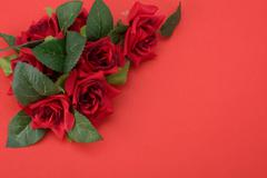 red background with floral decor. flowers are artificial. - stock photo