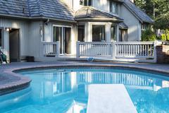 Backyard heated swimming pool Stock Photos