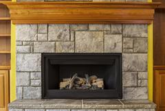 Natural gas insert fireplace with stone and wood Stock Photos