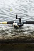 Fishing reel on log in lake Stock Photos