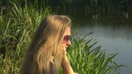 Young woman talking at phone near to a lake communication mobile connect blonde  Stock Footage