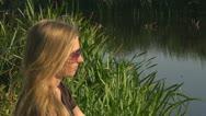 Beautiful woman relaxing rural lake female blonde girl pond sitting summer Stock Footage