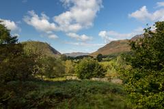 view over buttermere village to distant hills - stock photo