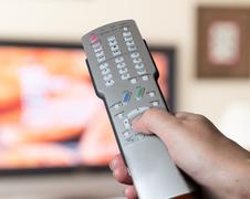 Stock Photo of close up of tv remote control with television