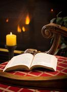 Paperback book open on chair by fire and candle Stock Photos
