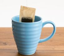 Brown organic green tea bag lowered in mug Stock Photos