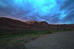 Dramatic red rock canyon at dusk with streaky storm clouds - stock photo