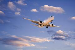 Commercial aircraft in evening sky Stock Photos
