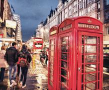 Red telephone booth in london on a crowded street at night Stock Photos