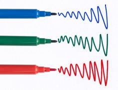 red green and blue felt tip pen squiggles on white paper. - stock photo