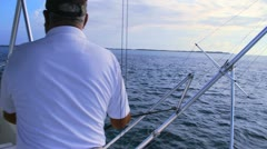 Captain extends outrigger on deep sea fishing boat Stock Footage
